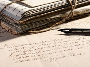Writing a letter concept with a retro fountain pen lying on a faded old letter and a stack of vintage aged and worn correspondence tied with string